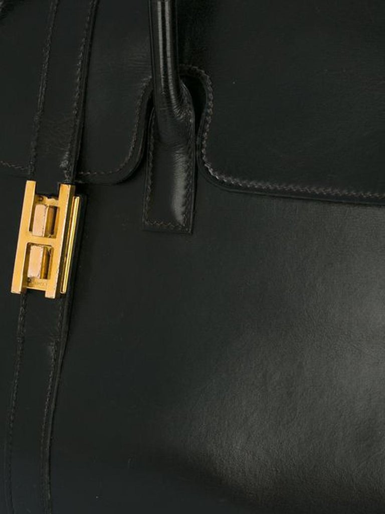 Hermès black box calf leather Drag tote bag featuring a foldover top with push-lock closure, two top handles ( 16,54in. (42cm) total length), plated gold-tone hardware and an internal zipped pocket.  Marked Hermès Paris In good vintage condition.