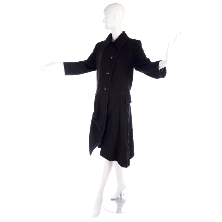 This is a very unique vintage Hermes coat in black cashmere.  The coat has a semi full skirted lower portion that is has an optional toggle at one side that creates an asymmetrical hemline!  The coat has flap pockets and comes from an estate we were