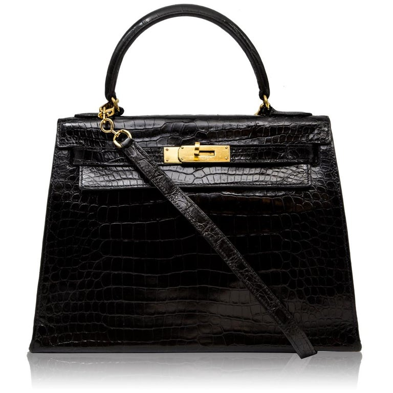 Crafted from black crocodile leather, this vintage 28cm Kelly Sellier bag is offset with gold-tone hardware and features a medium-handle, an adjustable crossbody shoulder strap and a goatskin-lined interior which opens to reveal a wide internal