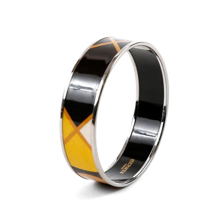 This authentic Hermès Black Enamel X Bracelet is in very good condition. Black enamel bracelet with X design in yellow and orange.  Silver tone edges.
