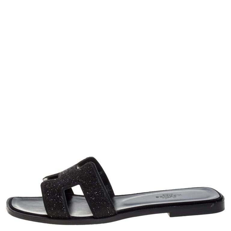 Put your best foot forward this season in these pretty Hermes sandals. These black Oran sandals have been crafted from glitter leather in Italy and they feature the iconic H on the vamps as well as insoles meant to provide comfort at every step.