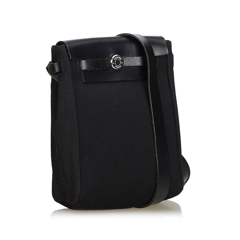 The Herbag features a canvas body, a leather shoulder strap, and a front flap with a front clasp closure. It carries as B+ condition rating.  Inclusions:  Dust Bag  Dimensions: Length: 20.00 cm Width: 15.00 cm Depth: 5.50 cm Shoulder Drop: 57.00
