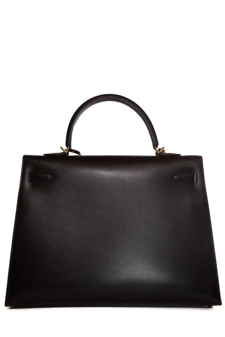 Hermès black swift leather 35cm Kelly Sellier with gold-tone hardware, single rolled top handle, single optional flat shoulder strap, three interior pockets; one with zip closure at back, tonal leather lining and turn-lock closure at front