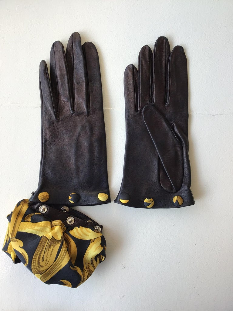Hermes Black Leather Gloves with Optional Silk Cuffs. The gloves are composed of a calfskin leather, with suede interior, and a signature Hermes print cuff. The silk scarf cuff features a black background with gold accents in undulating, floral