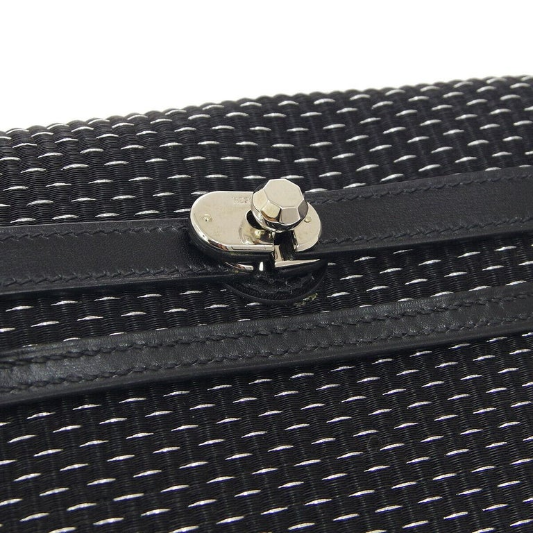 The Hermes Clutch of Understate Elegance.  This Hermes clutch is understated elegance at its best. Inspired by the classic Kelly design and crafted in black crinoline, this luxurious clutch features a turn-lock closure and palladium-tone hardware