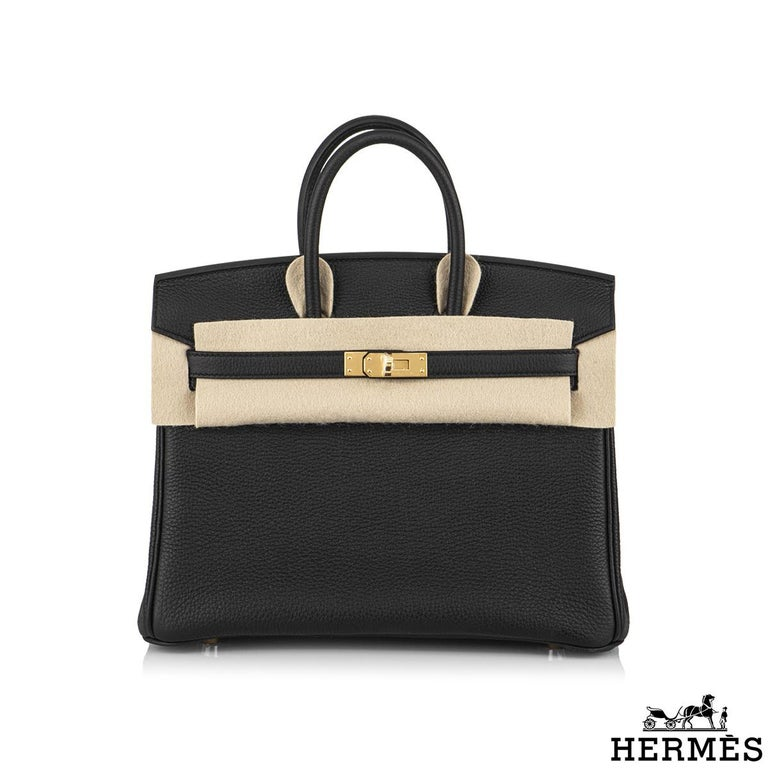 An exquisite Hermès 25cm Birkin bag. The exterior of this birkin is in black togo leather with tonal stitching. It features gold tone hardware with two straps and front toggle closure. The interior is lined with black chevre and has a zip pocket