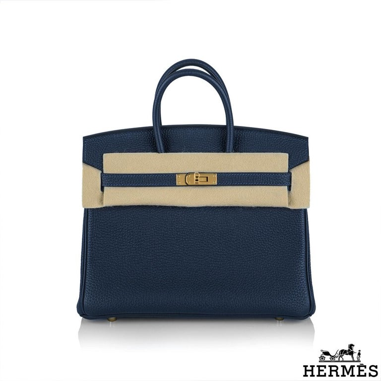 An exquisite Hermès 25cm Birkin bag. The exterior of this birkin is in bleu nuit togo leather with tonal stitching. It features gold hardware with two straps and front toggle closure. The interior is lined with Bleu Nuit chevre and has a zip pocket