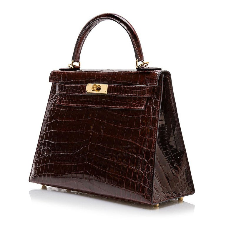 Crafted in France from Shiny Niloticus leather, a rare  Hermès skin, notorious for its large scales and noticeably glossy finish. this structured, Kelly Sellier bag features rigid corners and matching stitching with concealed piping. Featuring a