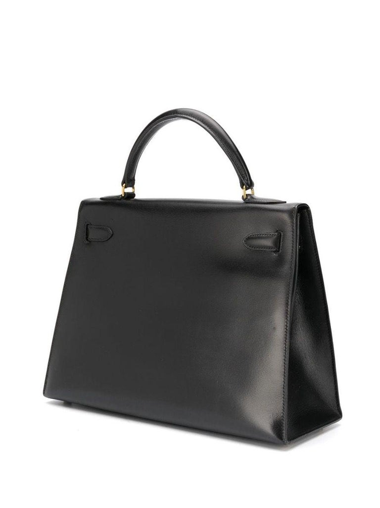 Meticulously crafted in France from smooth black box calf leather, a favoured Hermès hide for its smooth texture and glossy finish, this unique piece features a trapeze-shaped body, a medium top-handle and gold-tone metal accents. 32cm in width, the