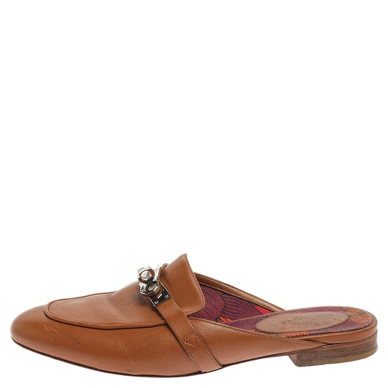Designed in a loafer style, these Oz mules are from the house of Hermes. They are beautifully crafted in brown leather with the signature twist-lock in palladium-plated metal on the vamps. Slip these flat mules on for a comfortable urbane