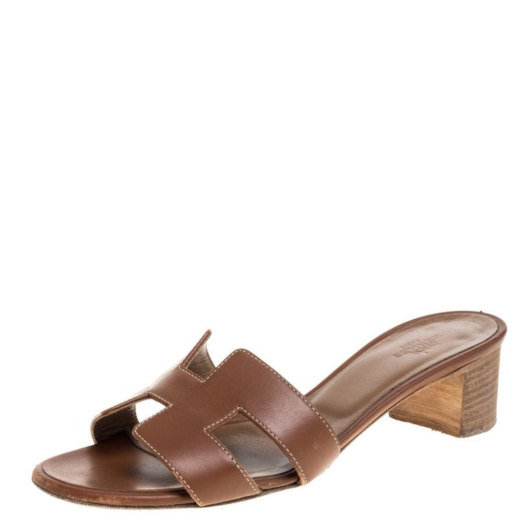 These brown leather slides from Hermès are a pair of simple and casual shoes. These slides have H straps on the vamps with contrasting white stitching. It is finished with open toes and 5 cm block heels.