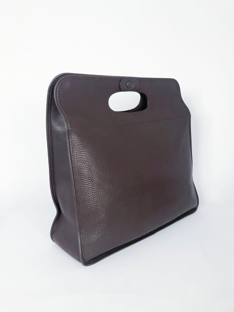 Hermès Brown leather tote bag with cut-out handles along the top of the bag. Button snap  closure at the center top. The interior is composed of the large main compartment with one zip pocket and one opened on.