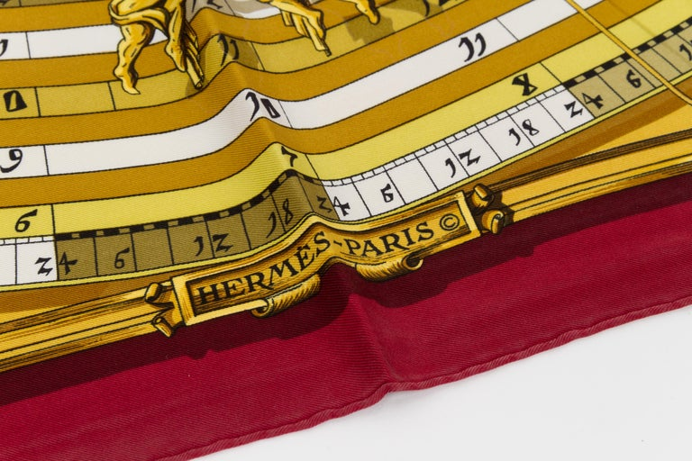 Hermes silk twill Astrologie scarf in burgundy with cream and gold accents. Hand-rolled edges. Minor wear.
