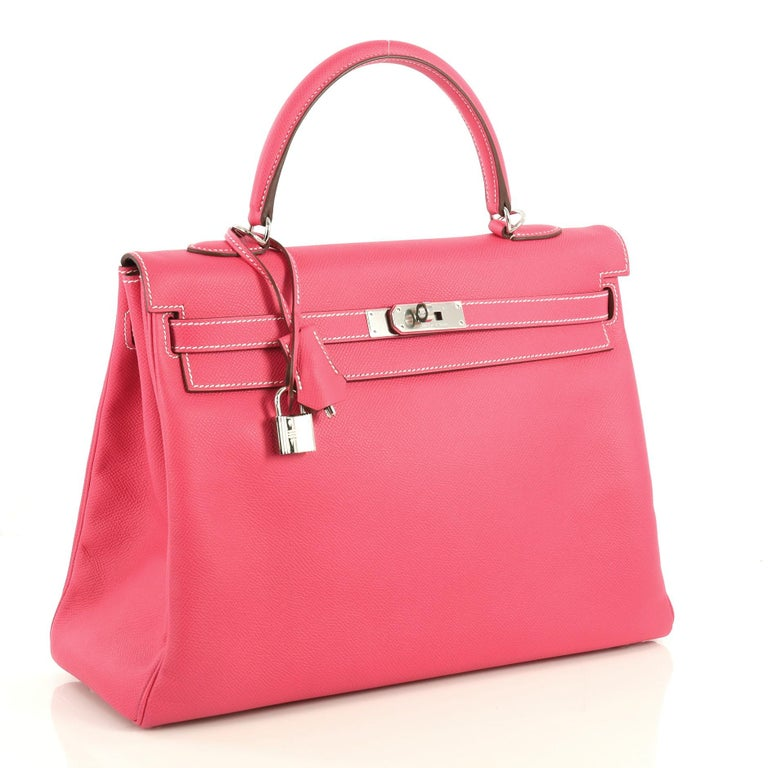 This Hermes Candy Kelly Handbag Epsom 35, crafted from Rose Tyrien pink Epsom leather, features a single rolled top handle, frontal flap, protective base studs, and palladium hardware. Its turn-lock closure opens to a Rubis Chevre leather interior