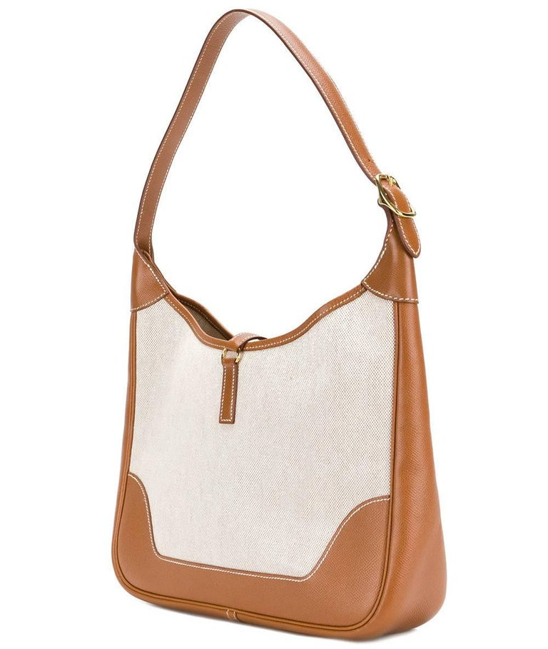 Classy Hermès beige canvas and brown leather zipped Hobo bag. It features an adjustable shoulder strap, a lobster clasp closure, a main internal compartment, stitching details and gold-tone hardware. It comes with its original dustbag. According to