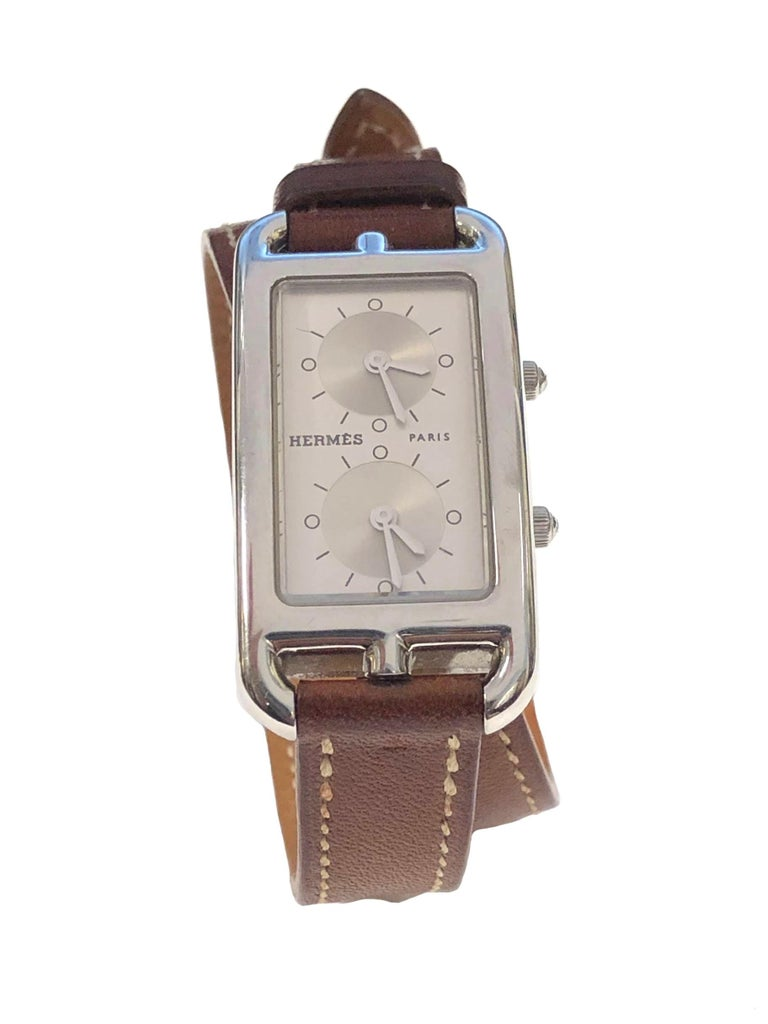 Circa 2018 Hermes Cape Cod Dual Time Zone Wrist Watch, Reference # CC3.210, 40 X 20 M.M. 2 Piece Stainless Steel case. @ independent Quartz Movements, Silver Dial. Original and near Unused Light Brown 7/16 inch wide Leather Wrap Around Strap with