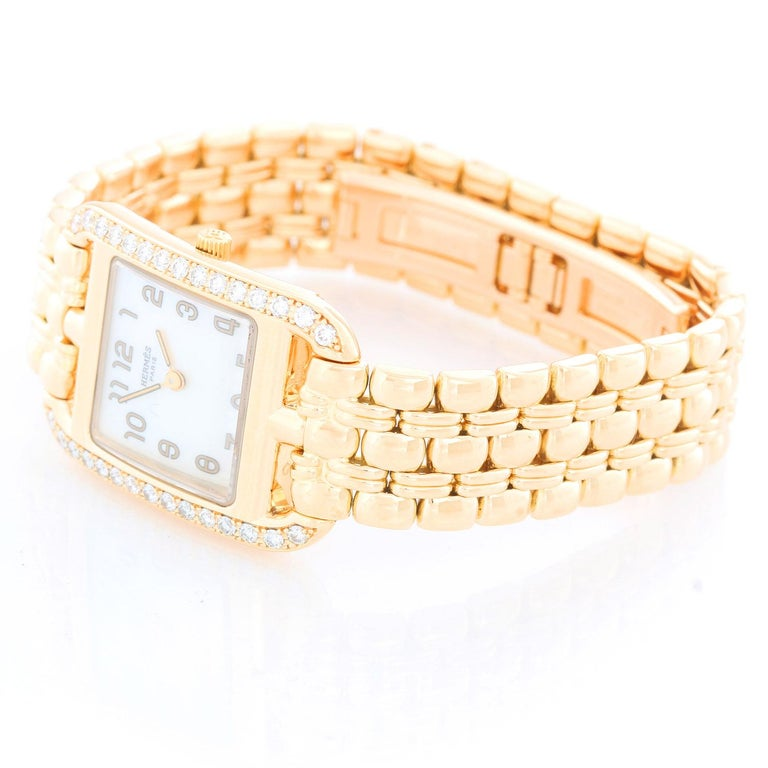 Hermes Cape Cod Yellow Gold Ladies  Watch CC1.288 - Quartz. 18K Yellow gold ( 23 x 23 mm ) with diamond bezel . White mother of pearl watch with Arabic numerals. 18K Yellow gold Hermes bracelet . Pre-owned with Hermes box and papers .