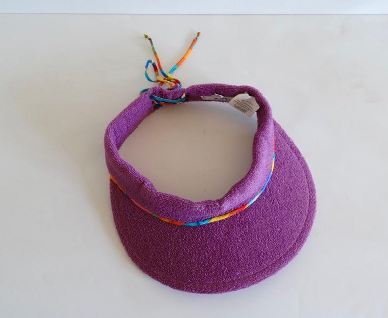 Stay chic while keeping those sun rays off your face with our lovely Hermès Paris Terry cloth sun visor. From their Casquette Oasis collection, this visor is a meduse purple with a silk twisted multi color lace up back detail. Sz 57 Head