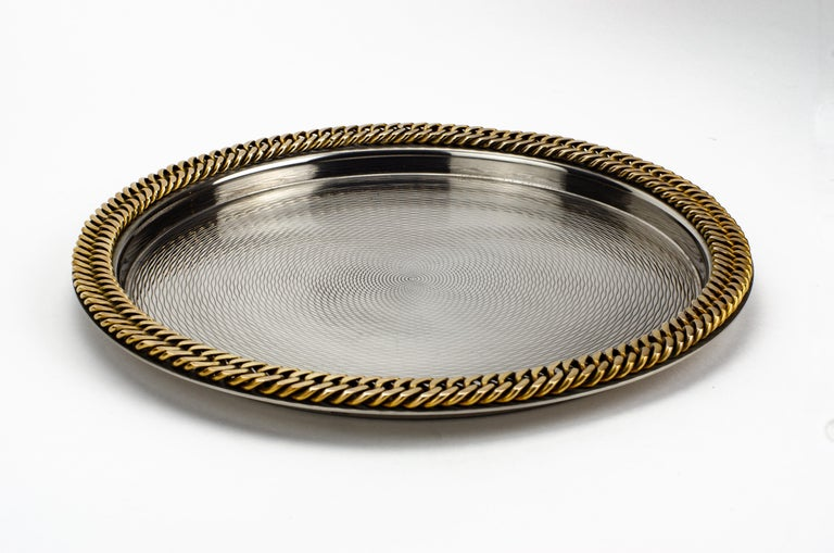 A finely executed tray by Hermès. Complete with a gilt chain link around the edge, as well as an engine-turned design engraved into the tray.