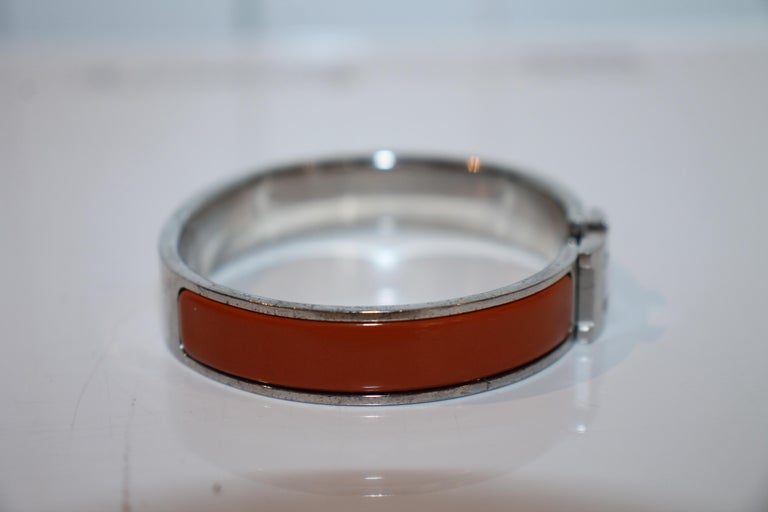 Palladium-plated Hermès Clic Clac H bracelet featuring brownish orange enamel inlays and hinged clip closure. (Size: 1)