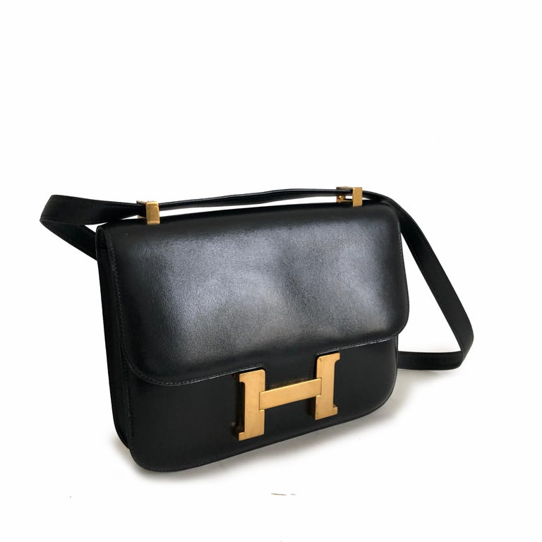 Hermes Constance Bag 23cm in Black Box Leather. Fully-lined with one zipper pocket. Adjustable strap allows wear on shoulder or by hand. Preowned/vintage with some signs of wear: light scratches/color loss to areas of hardware; fingernail scratches