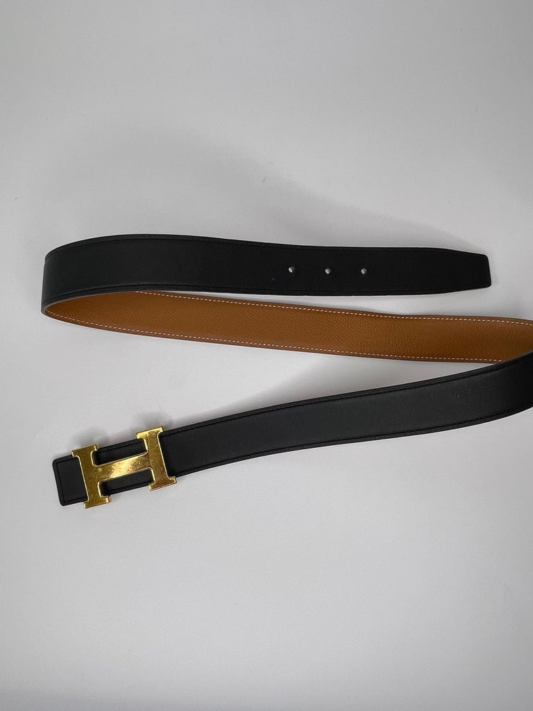 Authentic Hermes belt in very good conditions. Scuffs on buckle front and some marks and at the back. Leather strap pristine. This stylish reversible belt is crafted in polished calfskin leather in black, with a togo leather lining in brown and a