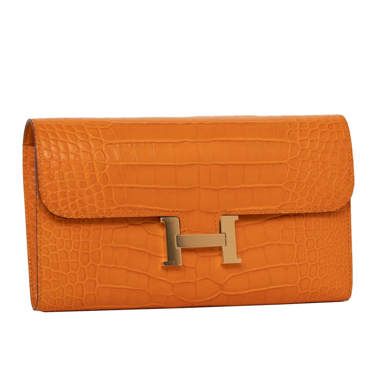Brand: Hermès  Style: Constance Wallet  Size: 20.5 L x 13 H x  2 D cm Color: Abricot Leather: Matte Alligator Hardware: Gold Stamp: 2018 C Other: 12 credit card slots, 2 bill pockets, zipped change purse, external pocket and palladium plated 'H'