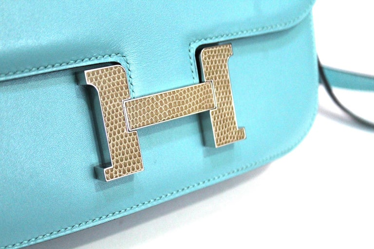 Pretty and original Hermes Constance small shoulder bag in Swift blue du nord leather, palladium inserts, convertible shoulder strap in blue leather to be worn on the shoulder or over the shoulder. The buckle is covered in python leather.