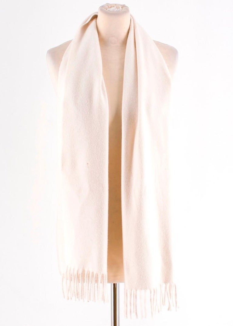 Hermes Cream Cashmere Scarf  -Cream cashmere scarf with tassels on both ends -Hole punched Hermes logo -Raw hem on all sides  Please note, these items are pre-owned and may show signs of being stored even when unworn and unused. This is reflected