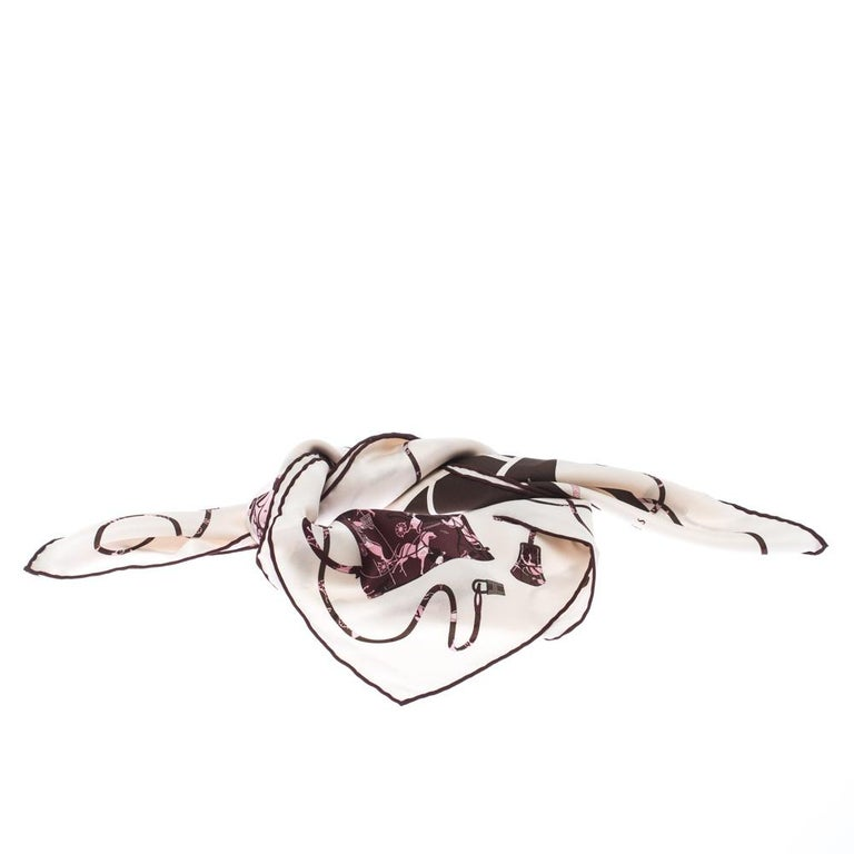 This silk Kelly scarf by Hermes will give you a chic look. Combining the lovely pink-brown Kelly print over a cream background, it also comes with 'Hermes Paris' printed over it. The scarf can be worn as a neck scarf, or placed as a bow on your