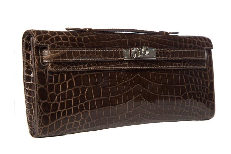 Hermès crocodile Kelly Cut Longue clutch Tonal stitching Palladium-plated hardware Single top handle Tonal leather interior lining Turn-lock closure Blind stamped Square Q from 2013 This item is previously worn with no major signs of wear. Item