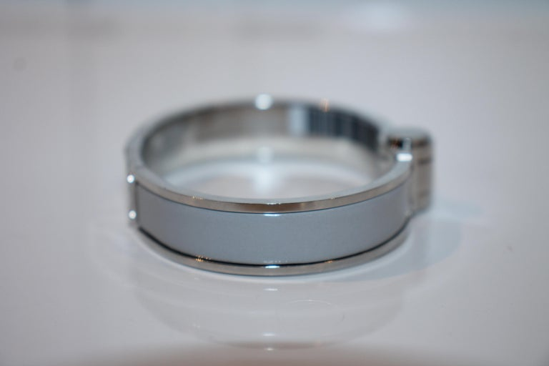 Palladium-plated Hermès oval hinged bracelet with an enamel inlay at a high polish finish with a hinged clip closure. (Size: 55)
