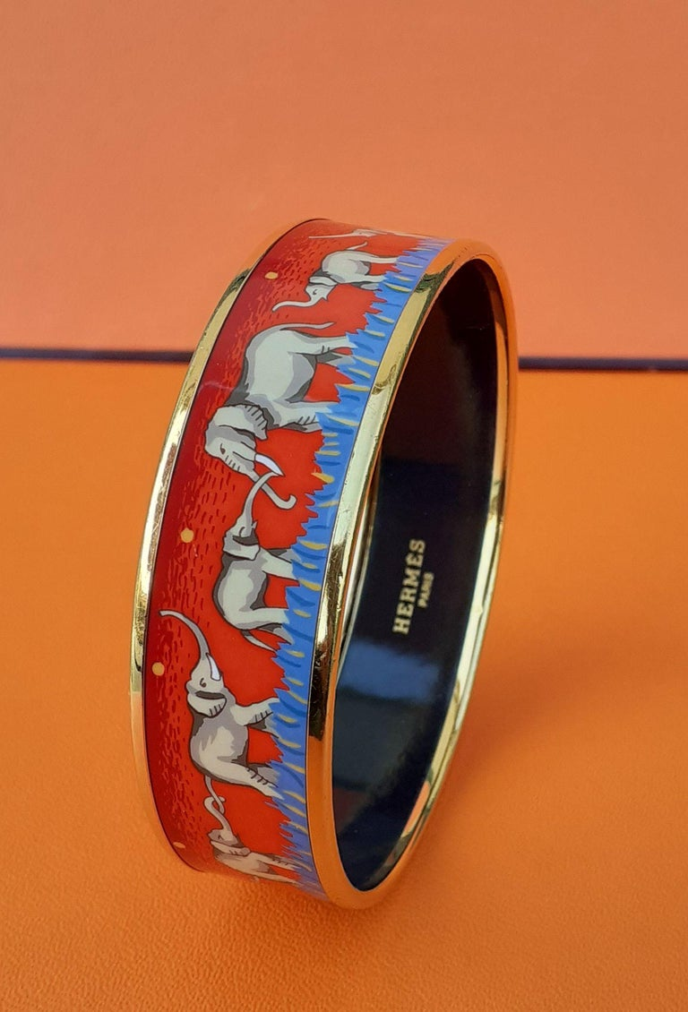 Gorgeous Authentic Hermès Bracelet  Pattern: Elephants Grazing  Hard to find ! One of the most thought after Hermès Bracelet. Rare in red !  Made in Austria + J  Made of printed Enamel and Gold Plated Hardware  Colorways: Red background with yellow
