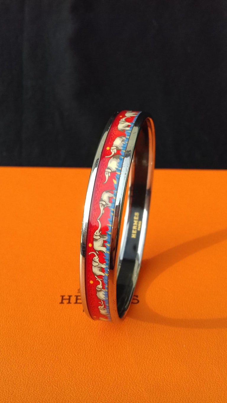 Gorgeous Authentic Hermès Bracelet  Pattern: Elephants Grazing  Hard to find ! One of the most thought after Hermès Bracelet  Made in Austria + L  Made of printed Enamel and Palladium Plated Hardware (silver-tone)  Colorways: Red background and
