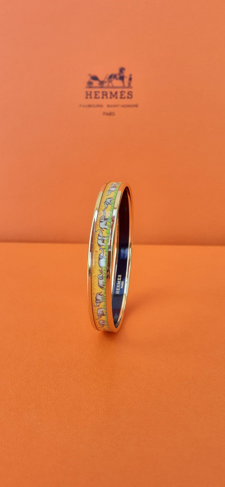 Gorgeous Authentic Hermès Bracelet  Pattern: Elephants Grazing  Hard to find ! One of the most thought after Hermès Bracelet  Made in Austria + F  Made of printed Enamel and Gold Plated Hardware  Colorways: Yellow background with discreet Pink peas,