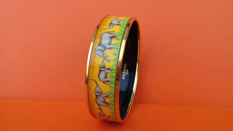 Gorgeous Authentic Hermès Bracelet  A grail ! Hard to find  Pattern: Elephants Grazing  Made in Austria + I  Made of printed Enamel and Gold Plated Hardware  Colorways: Yellow background with discreet Pink peas, Grey elephants and Green grass,