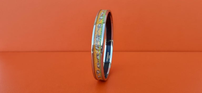 Gorgeous Authentic Hermès Bracelet  Pattern: Elephants Grazing  Hard to find ! One of the most thought after Hermès Bracelet  Made in Austria + F  Made of printed Enamel and Palladium Plated Hardware (Silver Tone)  Colorways: Yellow background with