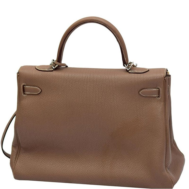 Inspired by none other than Grace Kelly of Monaco, Hermes Kelly is carefully hand stitched to perfection. This Kelly Retourne is crafted from Etoupe Togo leather and has palladium hardware. Retourne has a more casual look and is stitched on the