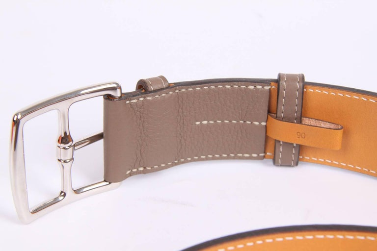 This belt has a beautiful name; it is the Hermès Etrivière Taurillon Clemence belt in taupe calfskin leather. And it is unisex.  Brand new item, comes with a little orange Hermès box and dustbag for the buckle. The buckle is crafted in silver-tone