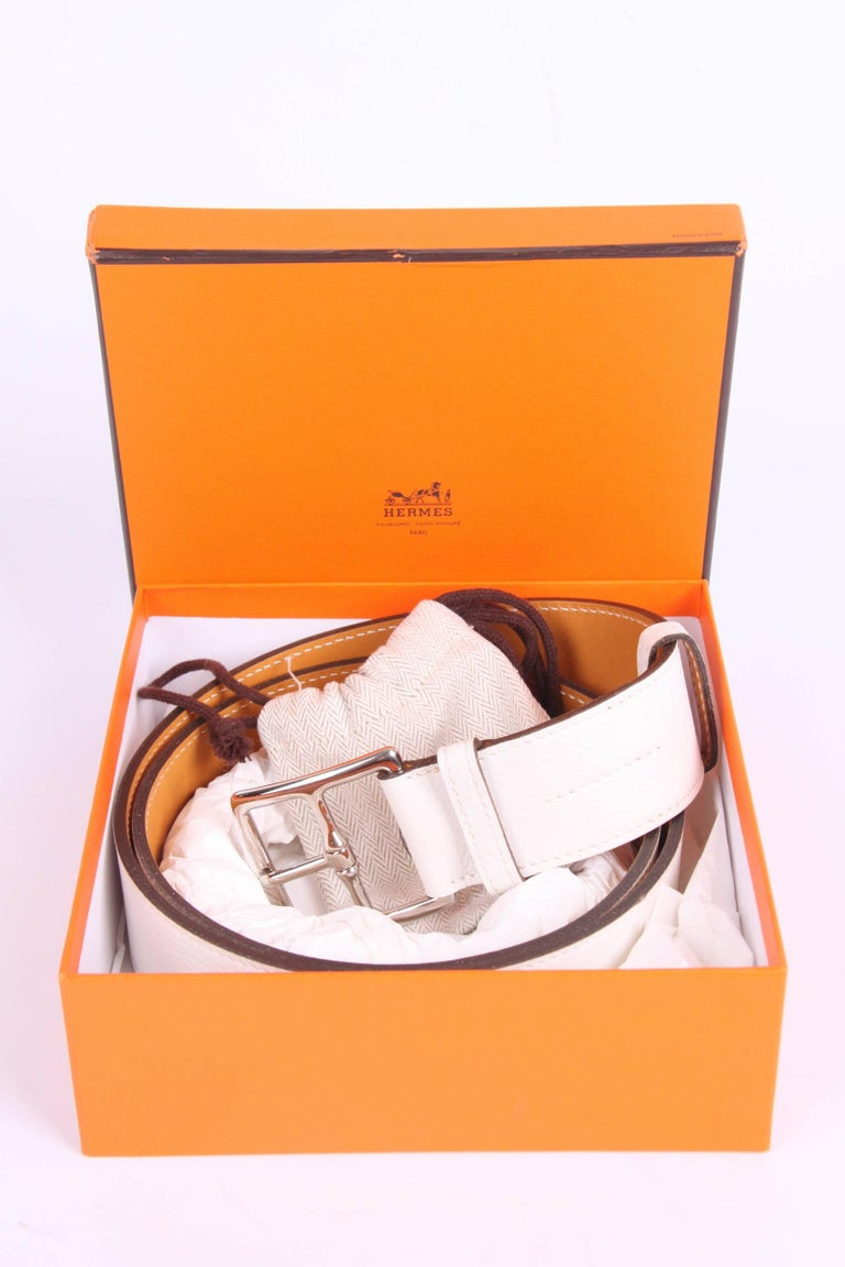This belt has a beautiful name; it is the Hermès Etrivière Taurillon Clemence belt in white calfskin leather. And it is unisex.  Brand new item, comes with a little orange Hermès box and dustbag for the buckle. The buckle is crafted in silver-tone