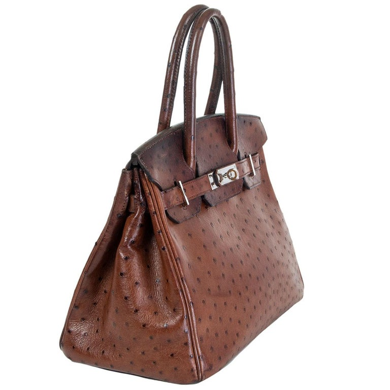 authentic Hermès Birkin 30 bag in Etrusque brown ostrich leather. Lined in brown chevre (goat skin) with an open pocket against the front and a zipper pocket against the back. Has been carried with patina allover, especially on the top part, back