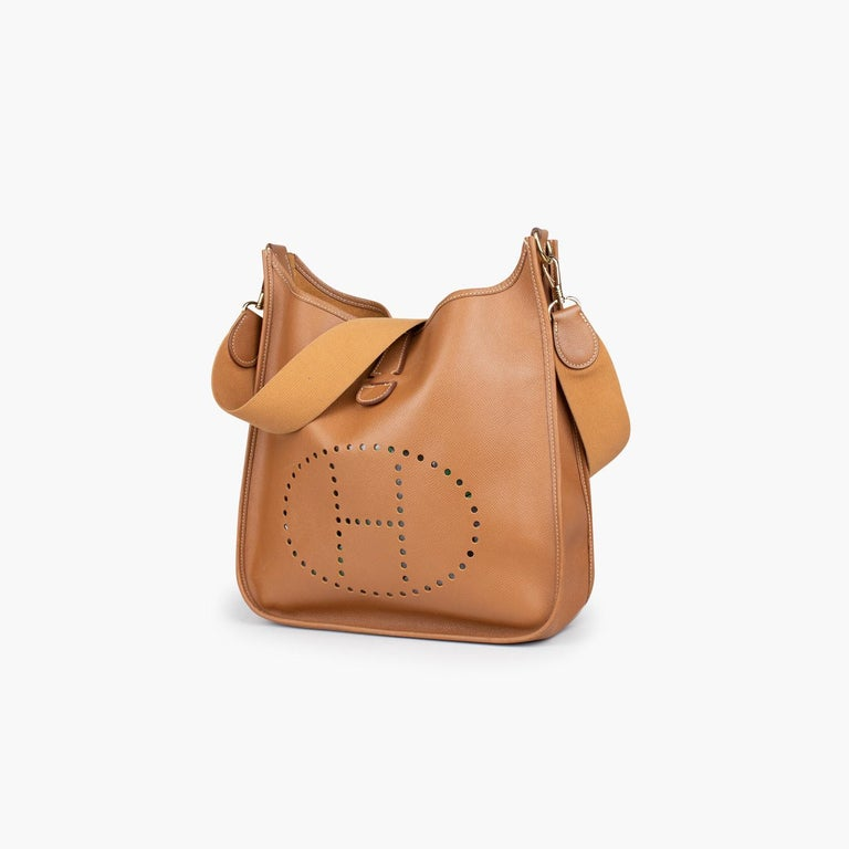 Gold Epsom leather Hermès Evelyne II PM with  – Gold-plated hardware – Tonal canvas shoulder strap – Perforated logo embellishment at front single slit pocket under flap – Tonal hide interior and snap closure at back  Overall Preloved Condition: