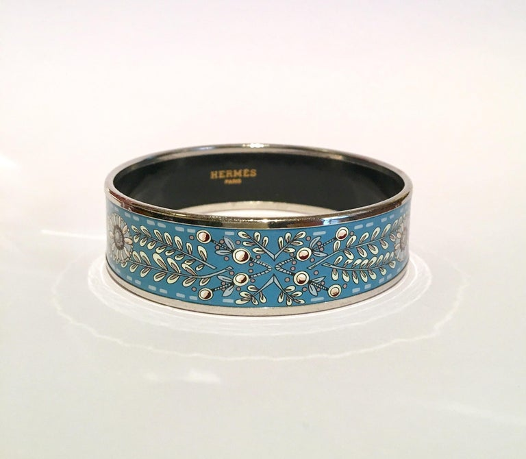 Excellent condition Hermès enamel Medium size bangle  Hermes bracelet in printed enamel representing flowers on a blue background  Palladium plated  Signed Hermès Made in Austria  With Dustbag & Box....   2.45″ diameter  0.40″ height Diamètre : 6,2
