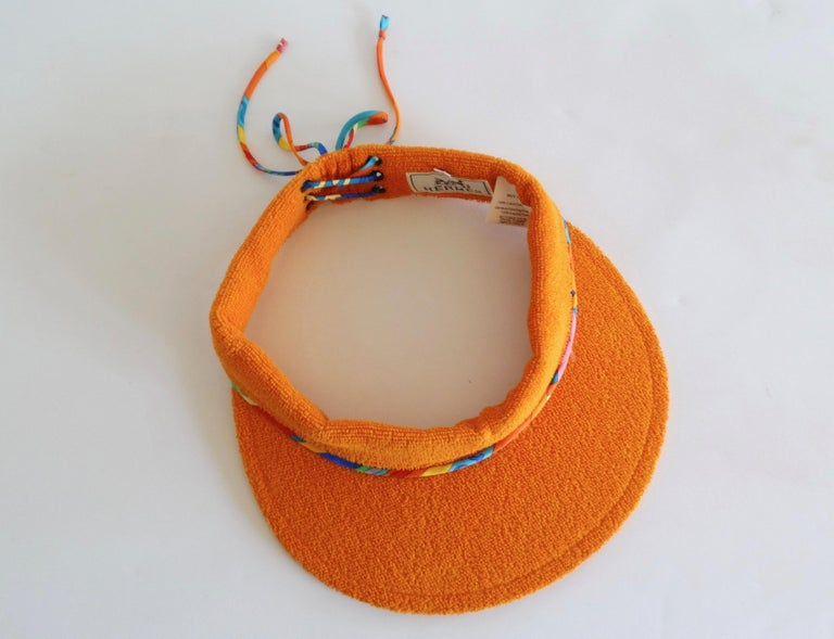 Stay chic while keeping those sun rays off your face with our lovely Hermès Paris Terry sun visor. From their Casquette Oasis collection, this visor is in Laterite (Hermès orange) with a silk twisted multi color lace up back detail. Sz 57 Head