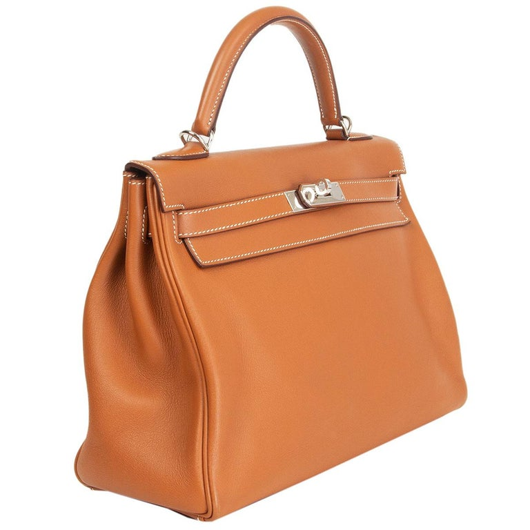 Hermes 'Kelly II 32 Retourne' bag in Gold (camel) Veau Swift leather with palladium-plated hardware. The interior is lined in Chevre (goat skin) with a divided open pocket against the front and a zipper pocket against the back. Has been carried and