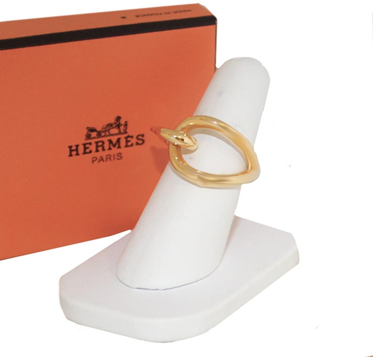 Hermes hallmarked  gold tone hook style tie ring an accessory to facilitate your scarf usage.  This scarf ring can be used with all different Hermes scarves.  It is excellent with plisse, cashmere stoles or pointu.   This hook style tie ring