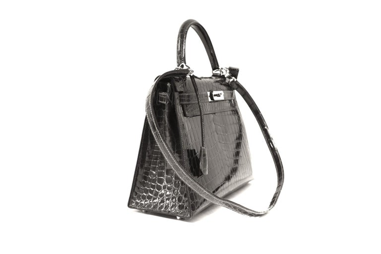 This authentic Hermès Graphite Crocodile 32 cm Kelly Bag is in pristine  condition.   Hermès bags are considered the ultimate luxury item the world over.  Hand stitched by skilled craftsmen, wait lists of a year or more are commonplace for the