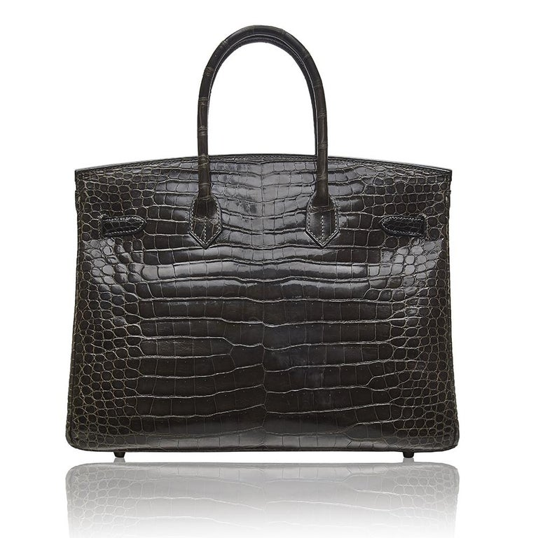 This Hermès Birkin is a truly spectacular, one-of-a-kind item and a must have for any serious collector. Crafted in a Gris Elephant Porosus Crocodile Leather and accented by silver-plated palladium hardware, this bag features two rolled leather