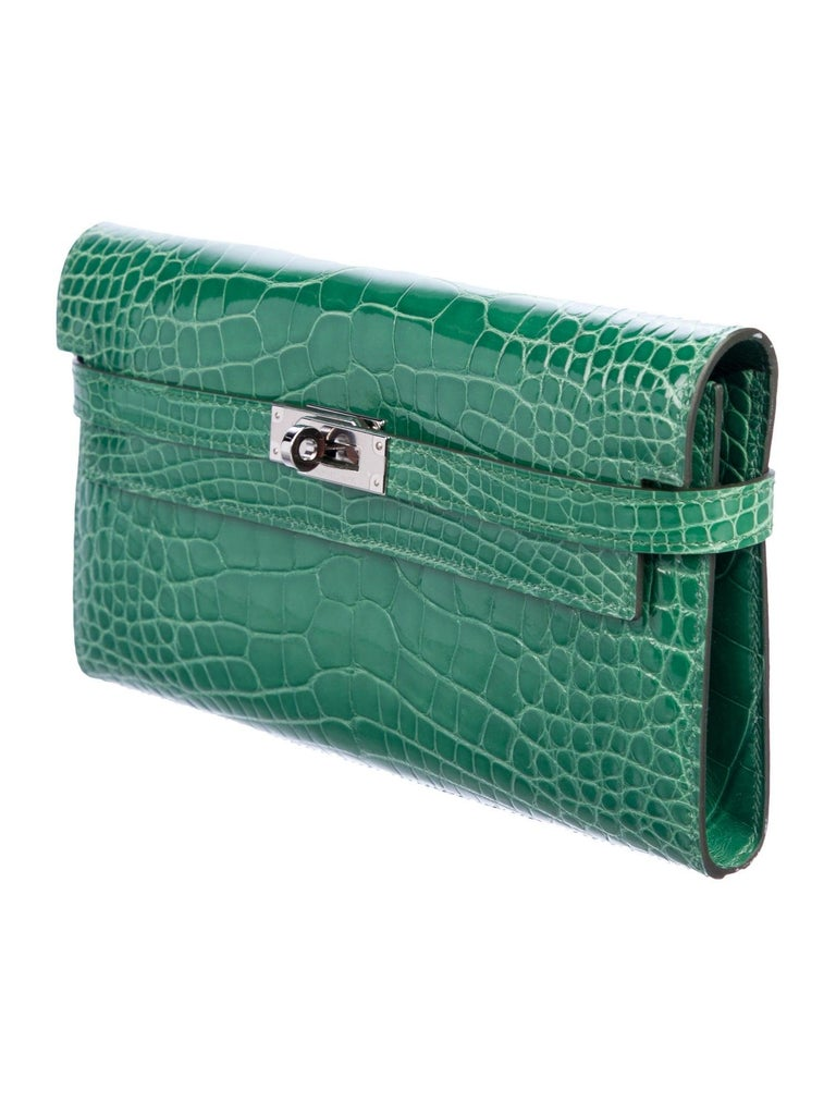 Hermes Green Alligator Exotic Palladium Silver Evening Kelly Clutch Wallet Bag in Box  Alligator  Palladium tone hardware Turnlock closure Leather lining Date code present Made in France Features zip closure, bill compartment and 12 card slots