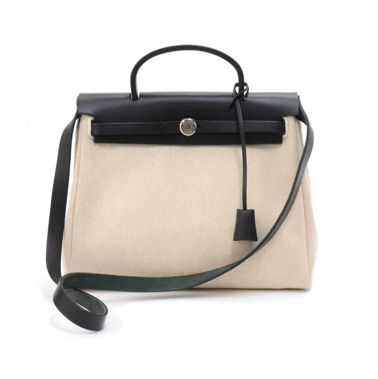 Hermes HerBag PM  2 in 1. Two canvas bags with leather. Leather pieces can be attached to either the beige or black canvas bags so you can enjoy 2 different looks. The bag can be carried on the shoulder  with the removale strap or in the hand. Very